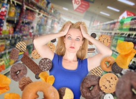 A woman has sweet food snacks around her on in a grocery store. She has fear and there are donuts and cookies. Use it for a health or diet concept.